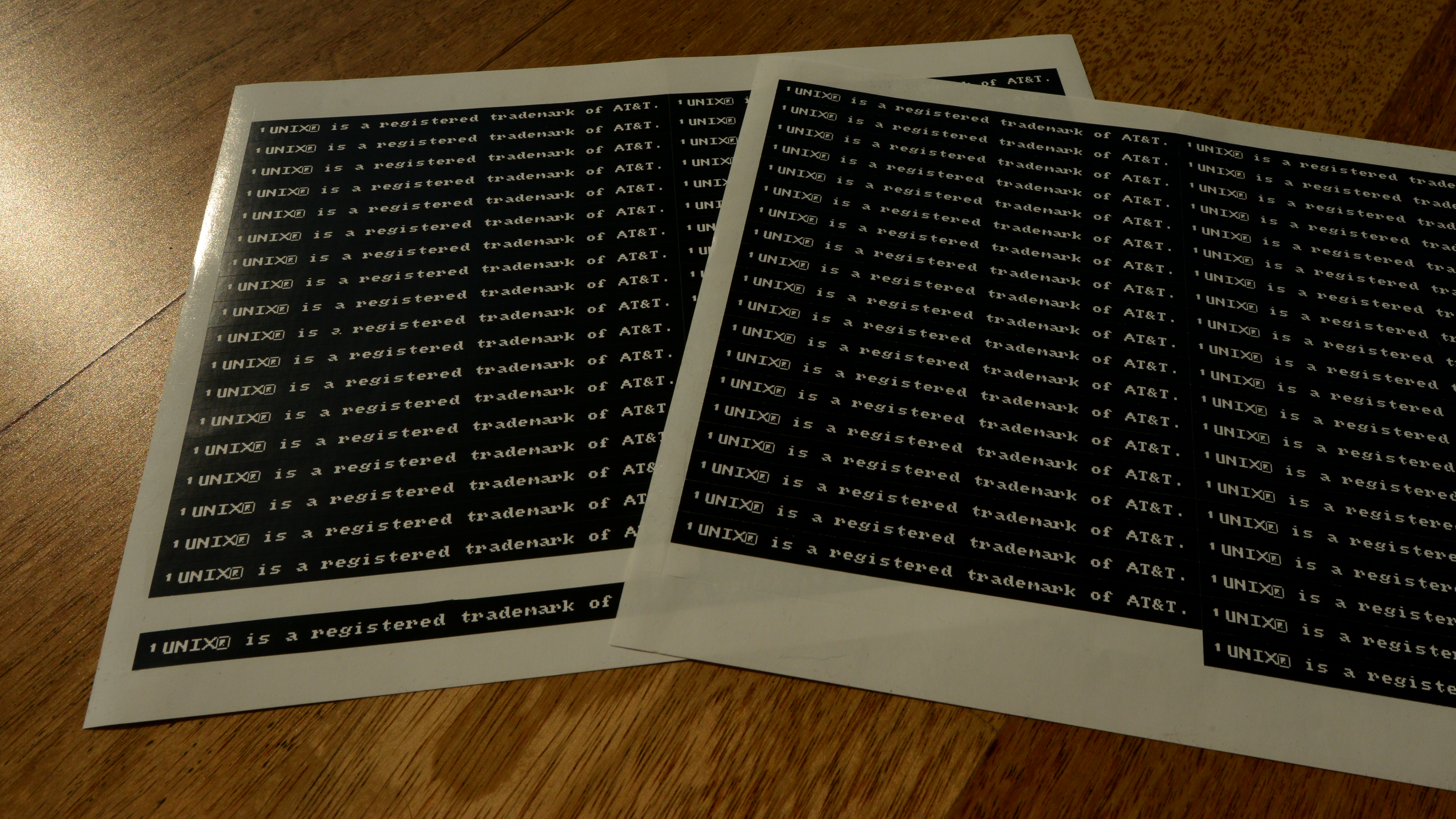 Two matt SRA3 sheets in the same spot, one on top of the other, at a slight angle, with ¹UNIX® is a registered trademark of AT&T. stickers tiled on them. The left is entirely opaque, but shows a tiny bit through the right.